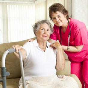 Friendly nurse cares for an elderly woman in a nursing home.